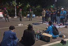 Dikawal Marinir Para Demonstran Melaksanakan Sholat Maghrib dengan Damai